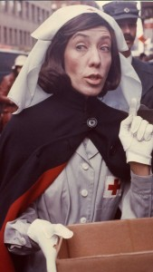 "Lily Tomlin as ""Red Cross Worker"". Handing out coffee and donuts to fans waiting in line to buy tickets to ""Appearing Nitely"" at the Biltmore. Young Judith Beasley ""Stay Put"" hair commercial from Emmy award winning special. © 2015 Lily Tomlin. All Rights Reserved."